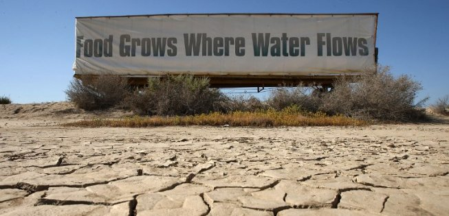 "Dry Farm Field With a Sign That Reads ""Food Grows Where Water Flows"""