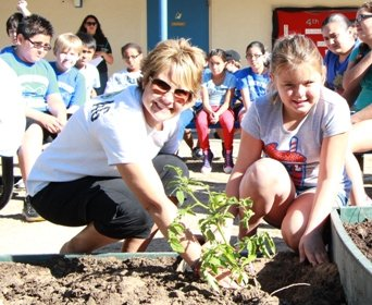 Rachael Barkley plants basil with Alice Byrne Elementary student