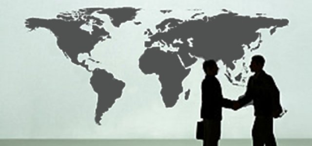 Picture of Two Silhouettes Shaking Hands in Front of a World Map
